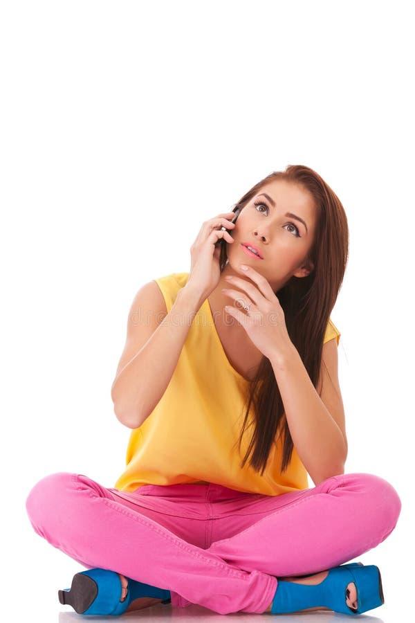 Femme inquiétée s'asseyant et parlant au téléphone photographie stock libre de droits