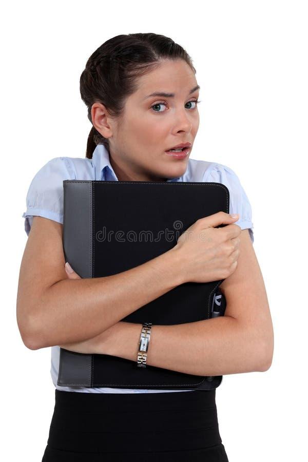 Femme inquiétée tenant le dossier photographie stock