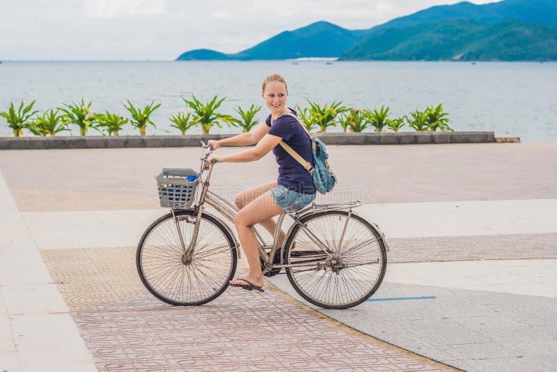 Femme insouciante avec l'équitation de bicyclette par la mer ayant l'amusement et le SMI photographie stock libre de droits