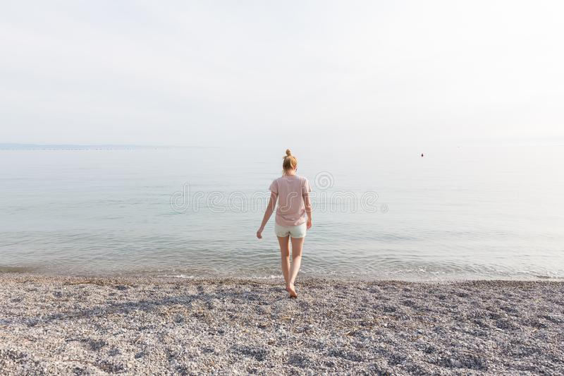 Femme insouciante heureuse appréciant la promenade de coucher du soleil sur la plage blanche de Pabbled photographie stock libre de droits