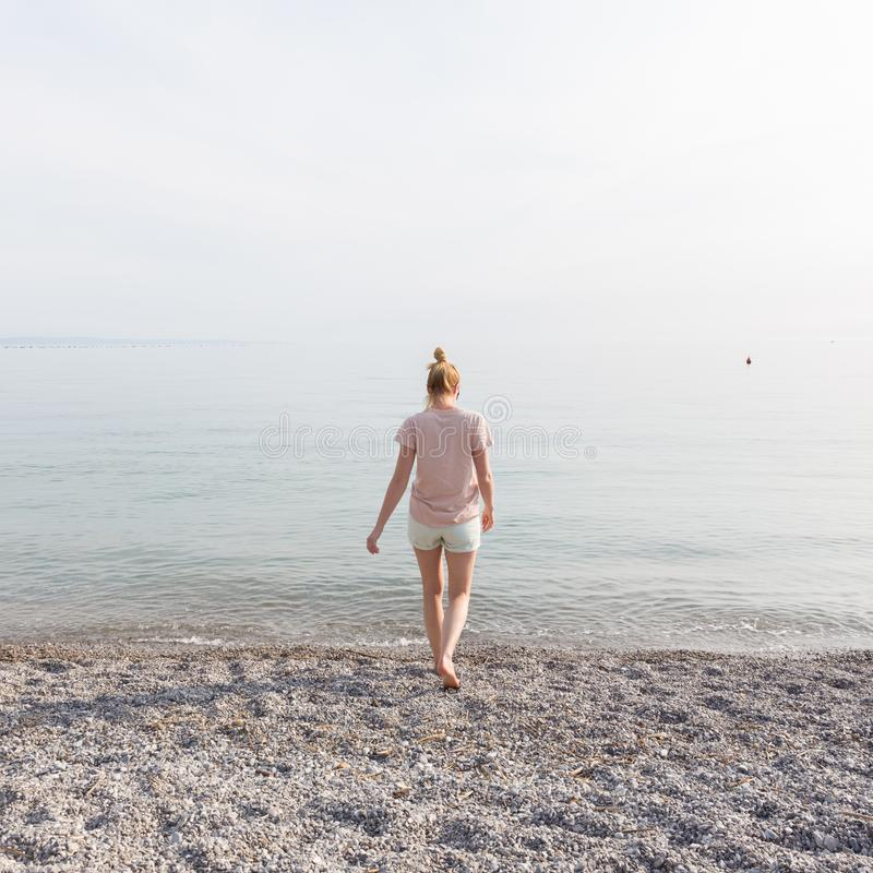 Femme insouciante heureuse appréciant la promenade de coucher du soleil sur la plage blanche de Pabbled photos stock