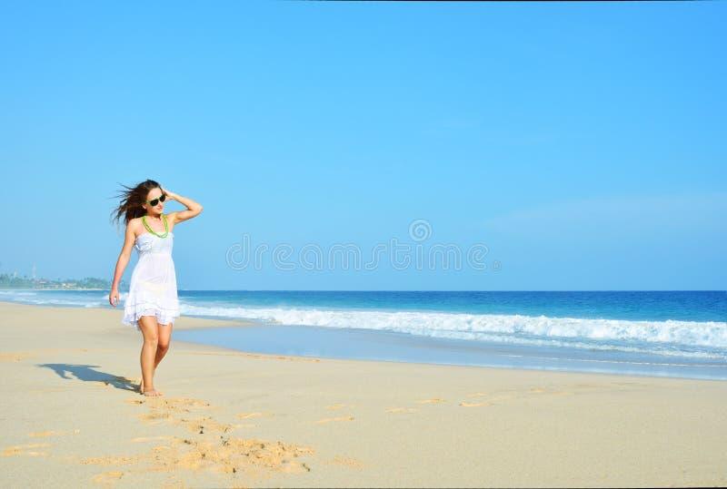 Femme insouciante heureuse marchant sur la plage célébrant sa liberté Fond de femme d'été de l'océan et du sable images libres de droits