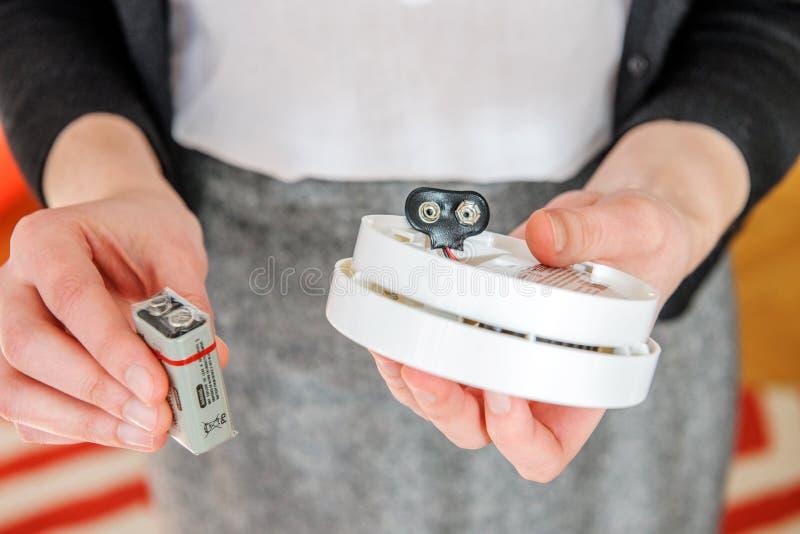 Femme installant la batterie de 9 volts dans le détecteur de fumée photos libres de droits
