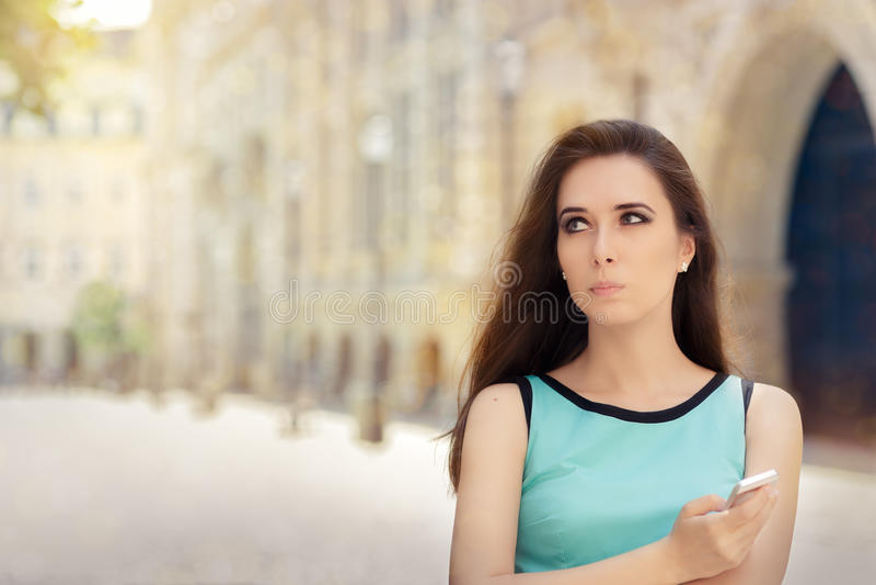 Femme irrésolue avec Smartphone dans la ville image libre de droits