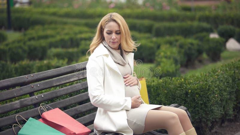 Femme irritée attendant le banc se reposant de bébé, sacs à provisions de lancement, fatigue image stock