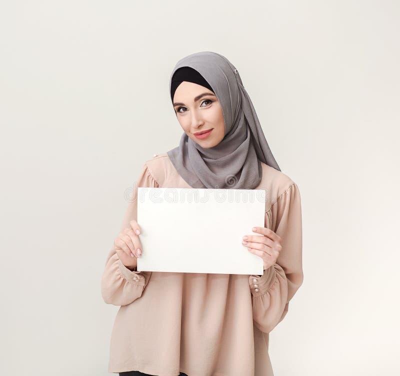 Femme islamique avec le conseil vide sur le blanc photos libres de droits