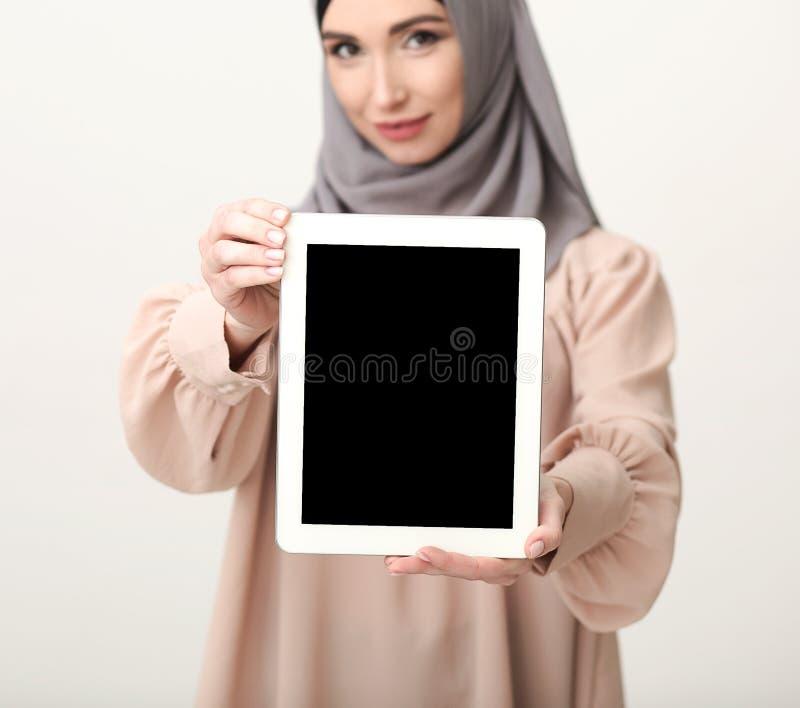 Femme islamique montrant le comprimé avec l'écran vide image stock