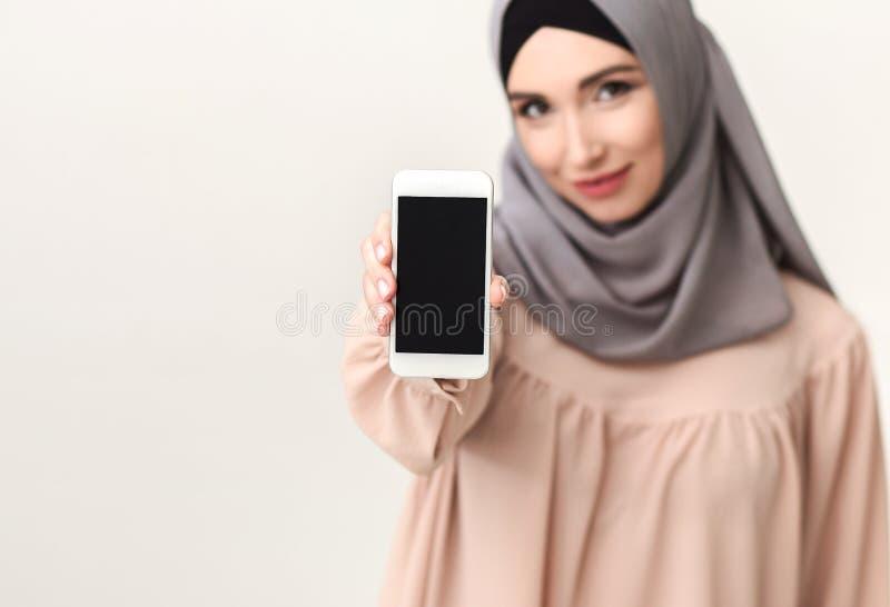 Femme islamique montrant le téléphone portable avec l'écran vide photo libre de droits