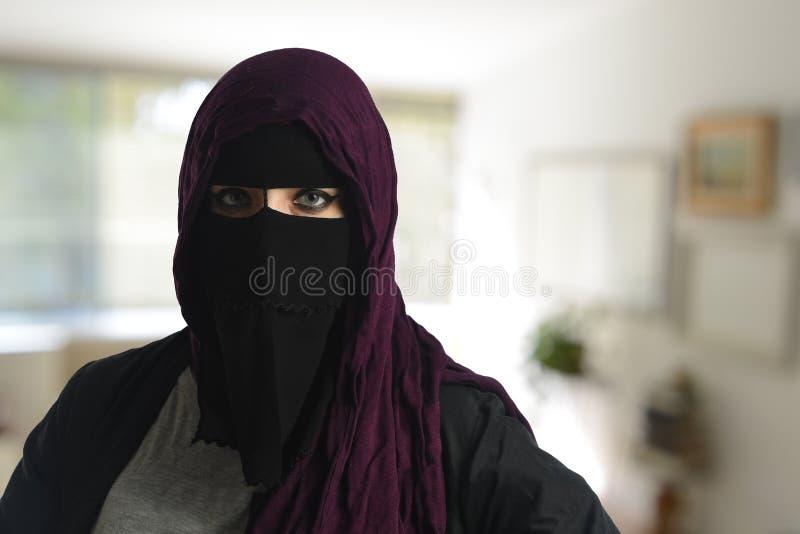Femme islamique portant un burqa image stock