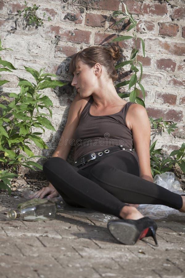 Femme ivre au mur de briques photos stock