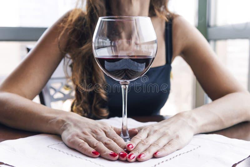 Femme ivre s'asseyant à une table et tenant un verre de fin de vin  Alcoolisme femelle photos libres de droits