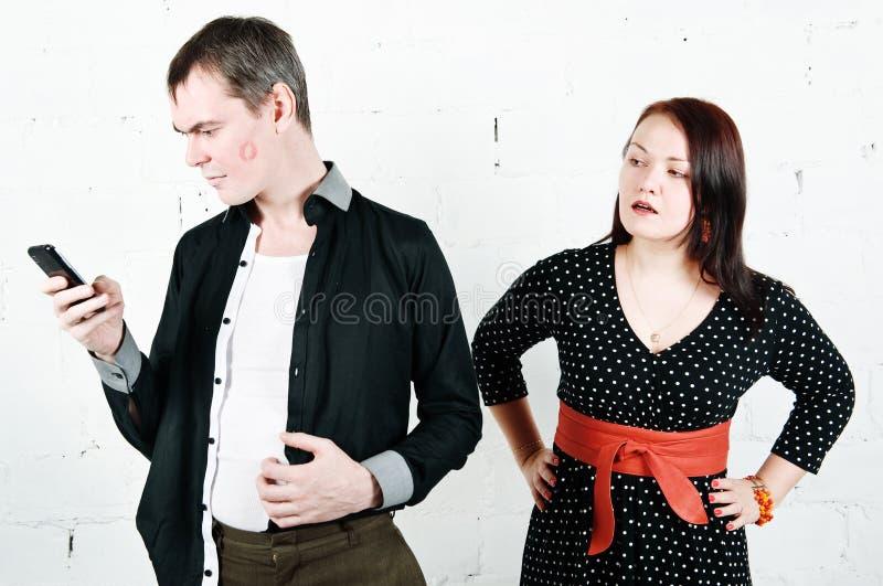 Femme jalouse regardant son homme avec le téléphone photo stock