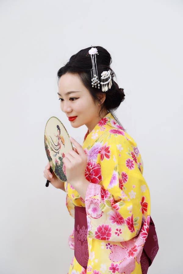 Femme japonaise asiatique traditionnelle avec le kimono avec une fan en main sur le fond blanc d'isolement photos stock