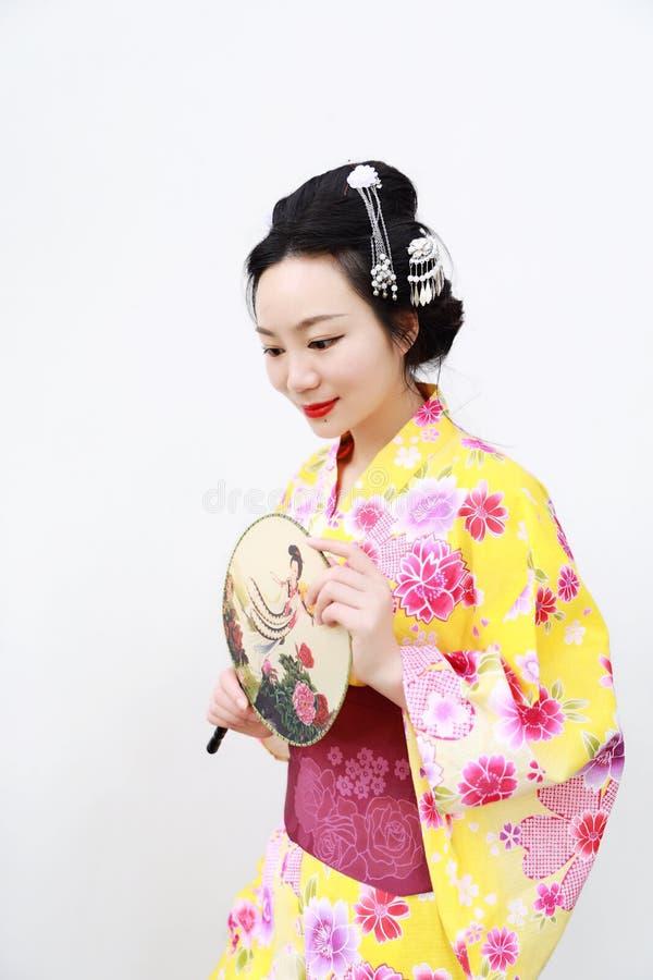 Femme japonaise asiatique traditionnelle avec le kimono avec une fan en main sur le fond blanc d'isolement photographie stock
