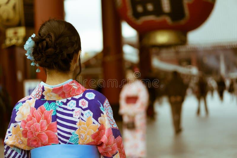 Femme japonaise traditionnelle utilisant un kimono regardant l'entrée du temple de Senso-JI, Asakusa, Tokyo, Japon photographie stock libre de droits