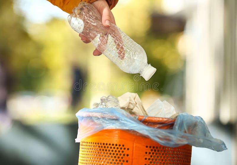 Femme jetant la bouteille en plastique dans la poubelle de déchets dehors images libres de droits