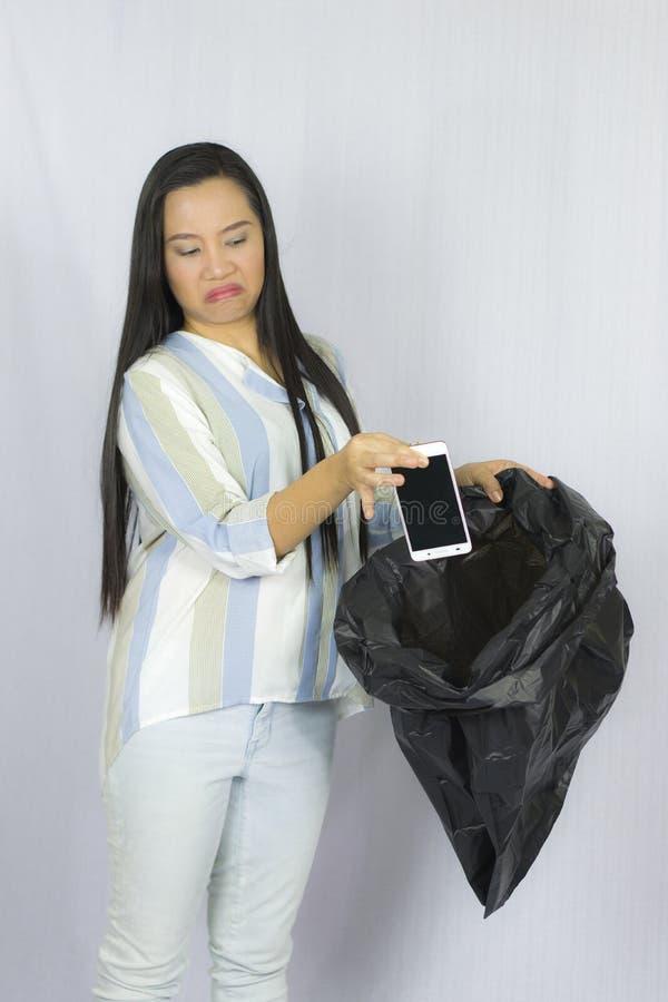 Femme jetant son t?l?phone dans le sac de d?chets, pose d'isolement sur le fond gris photo stock