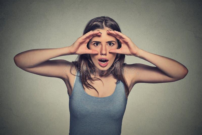 Femme, jetant un coup d'oeil par des doigts comme des jumelles étonnée choquée image libre de droits
