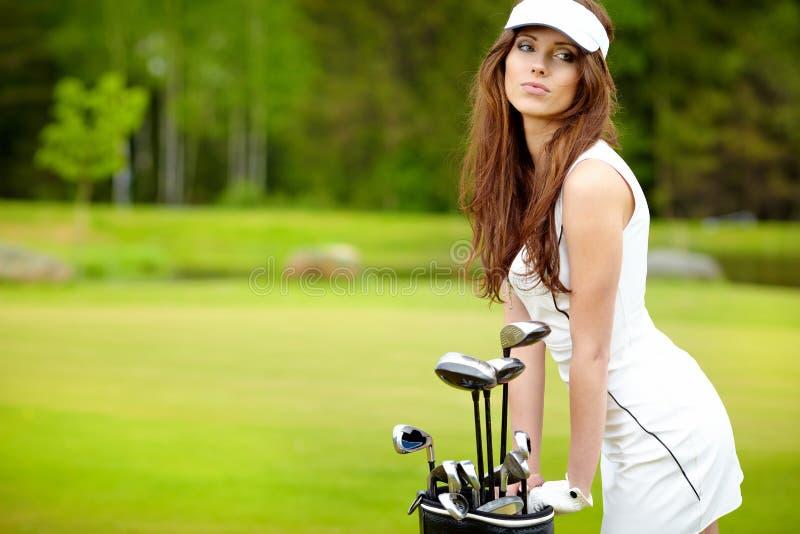 Femme jouant au golf sur un vert photographie stock