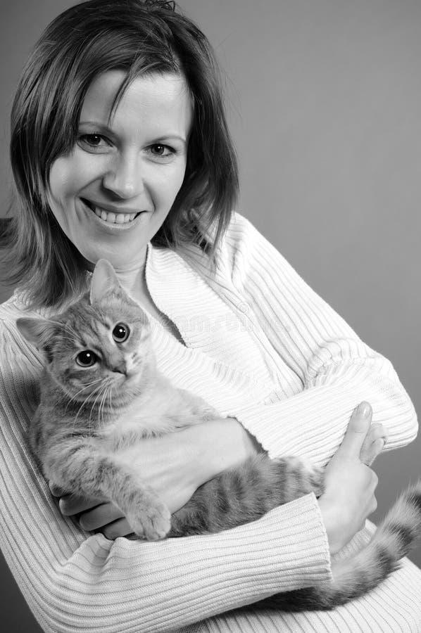 Femme jouant avec le chat image stock