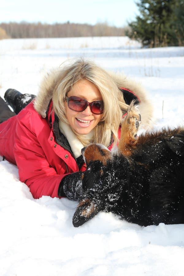 Femme jouant avec le crabot en hiver image stock