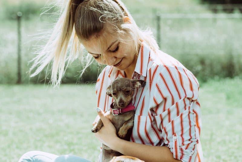 Femme jouant avec le petit chien dehors image libre de droits