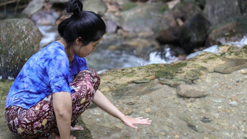Femme jouant des mains sur l'eau dans une cascade image stock