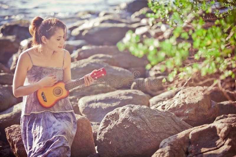 Femme jouant l'ukulélé sur la plage photographie stock libre de droits