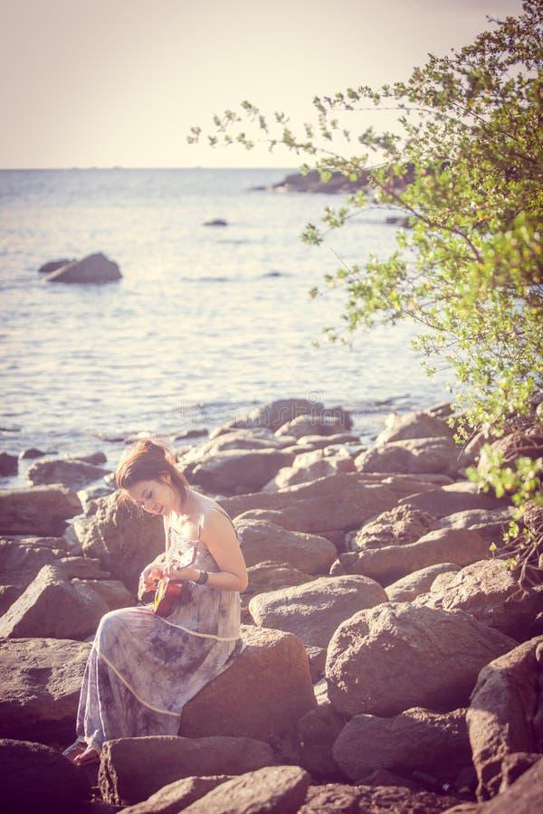 Femme jouant l'ukulélé sur la plage image libre de droits