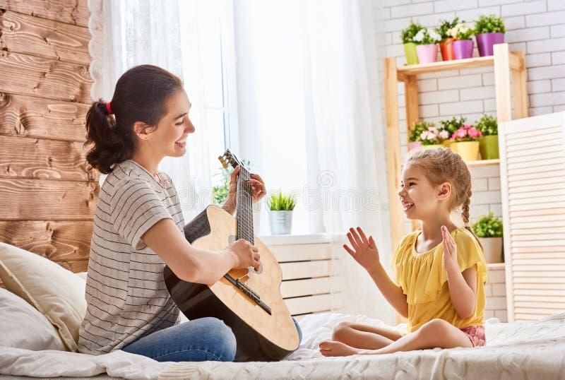 Femme jouant la guitare pour la fille d'enfant photos libres de droits
