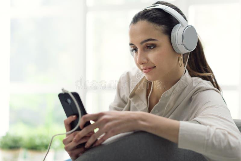 Femme jouant la musique sur son smartphone image stock