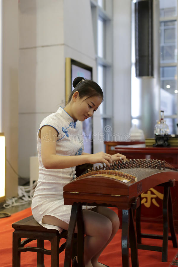Femme jouant le guqin chinois image stock