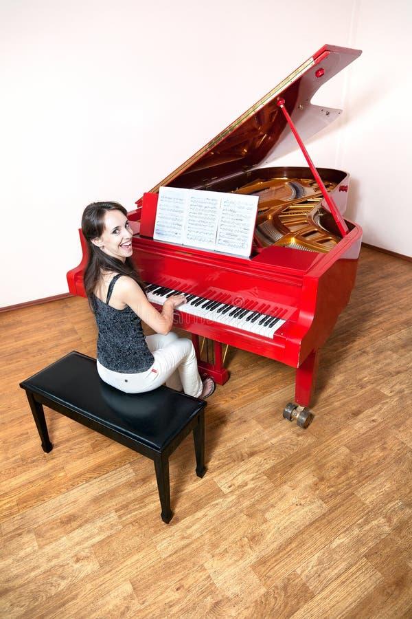 Femme jouant le piano à queue rouge images libres de droits