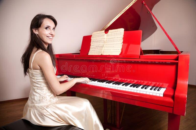 Femme jouant le piano à queue rouge photo libre de droits