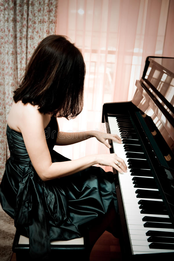 Femme jouant le piano image stock