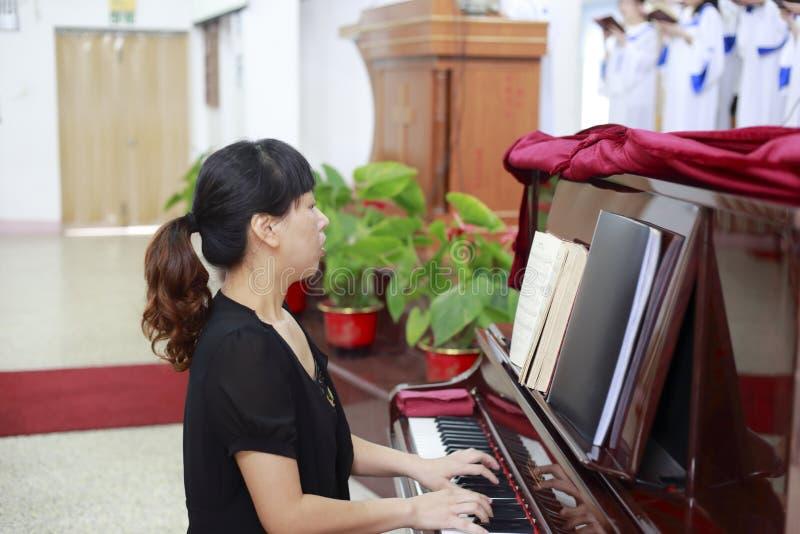 Femme jouant le piano dans l'église image libre de droits
