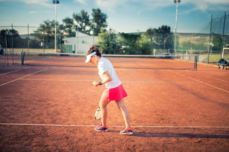 Femme jouant le tennis sur la cour d'argile, avec l'équipement sportif et le mode de vie sain photographie stock