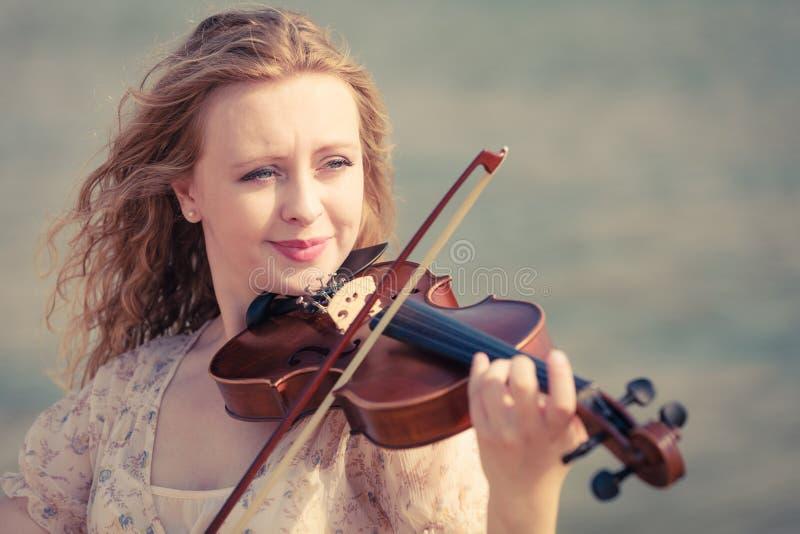 Femme jouant le violon sur le violon près de la plage images libres de droits