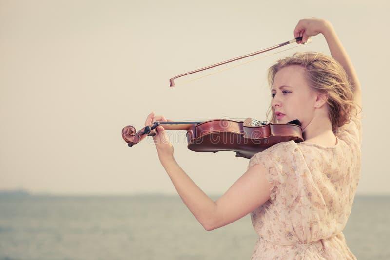 Femme jouant le violon sur le violon près de la plage image libre de droits