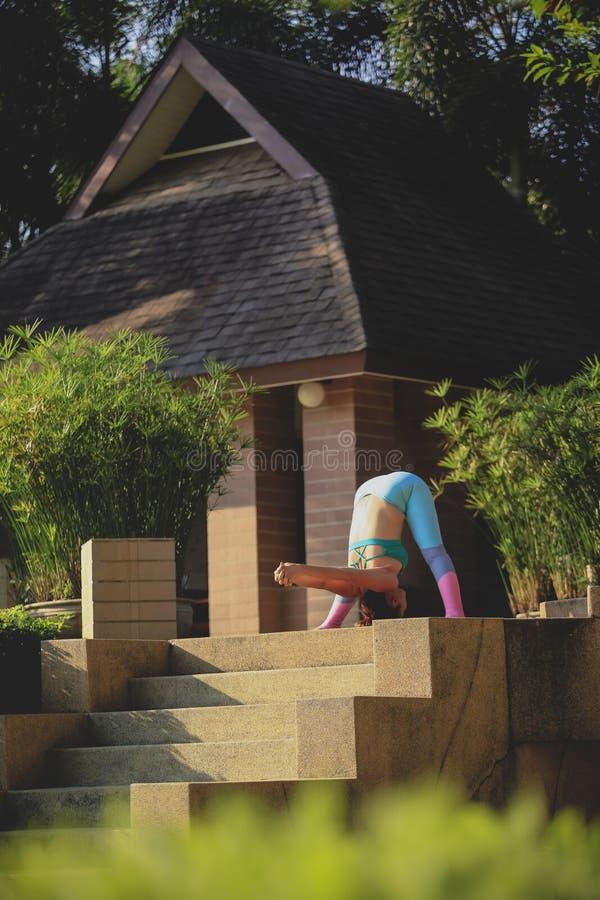 Femme jouant le yoga extérieur de la terrasse à la maison photographie stock