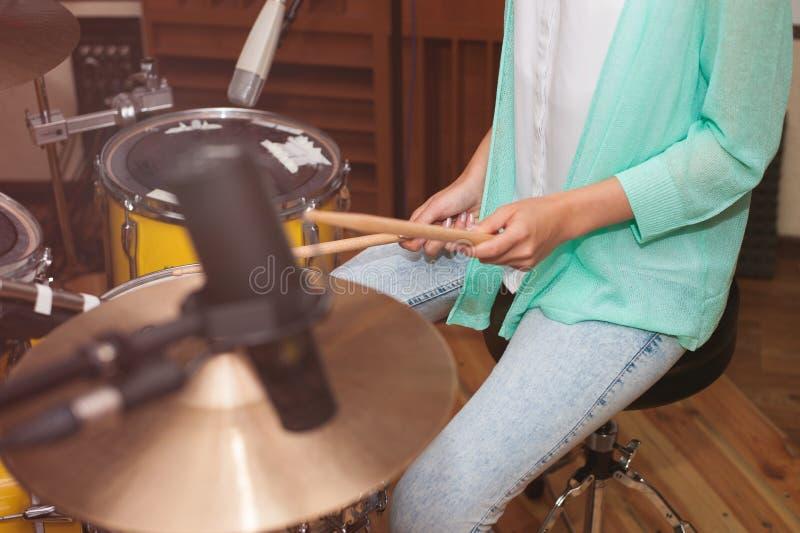 Femme jouant les tambours, enregistrement de studio/temps de répétition photographie stock libre de droits