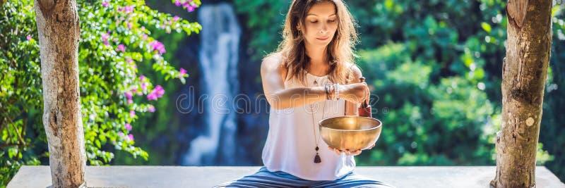 Femme jouant sur la cuvette tibétaine de chant tout en se reposant sur le tapis de yoga contre une cascade Vintage tonned Belle f photographie stock