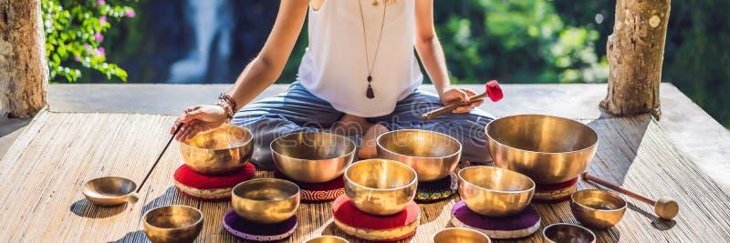 Femme jouant sur la cuvette tibétaine de chant tout en se reposant sur le tapis de yoga contre une cascade Vintage tonned Belle f photos libres de droits