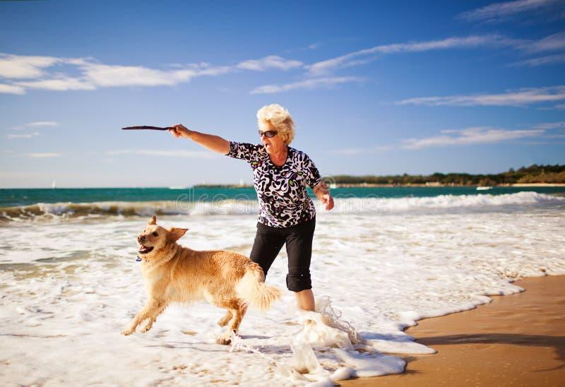 Femme jouant sur la plage avec le chien d'arrêt d'or image stock