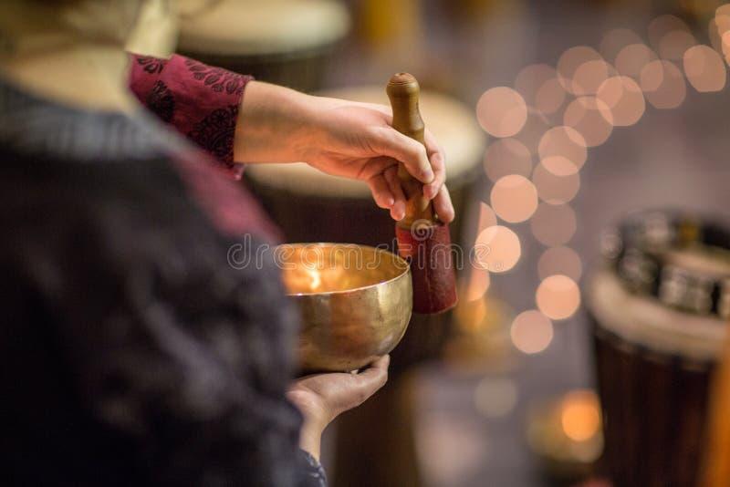 Femme jouant sur une cuvette tibetian de chant image stock