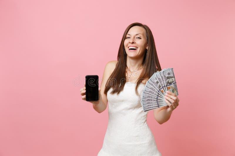 Femme joyeuse de jeune mariée dans la robe de mariage tenant un bon nombre de paquet de dollars, argent d'argent liquide, télépho photo stock