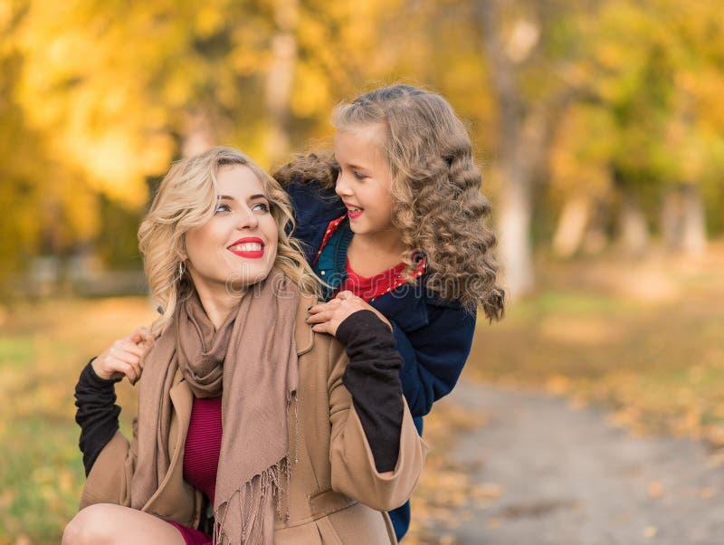 Femme joyeuse heureuse ayant l'amusement avec sa fille dans la couleur d'automne photo libre de droits