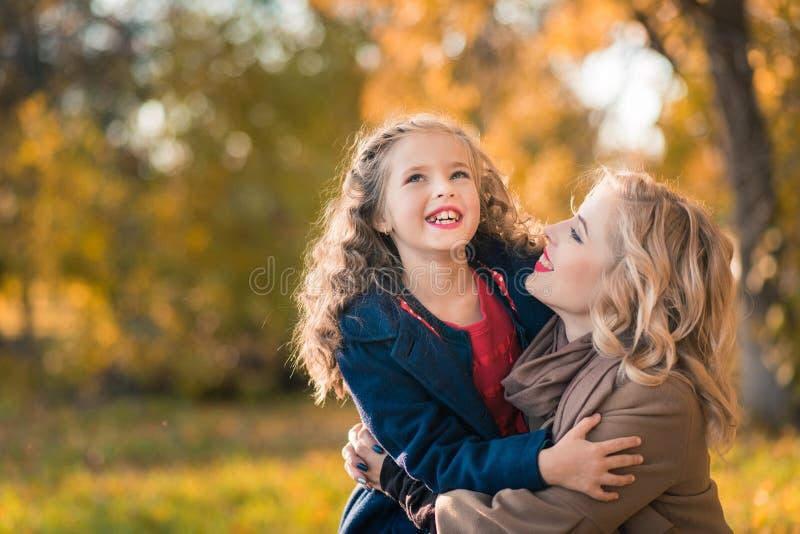 Femme joyeuse heureuse ayant l'amusement avec sa fille dans la couleur d'automne photos stock