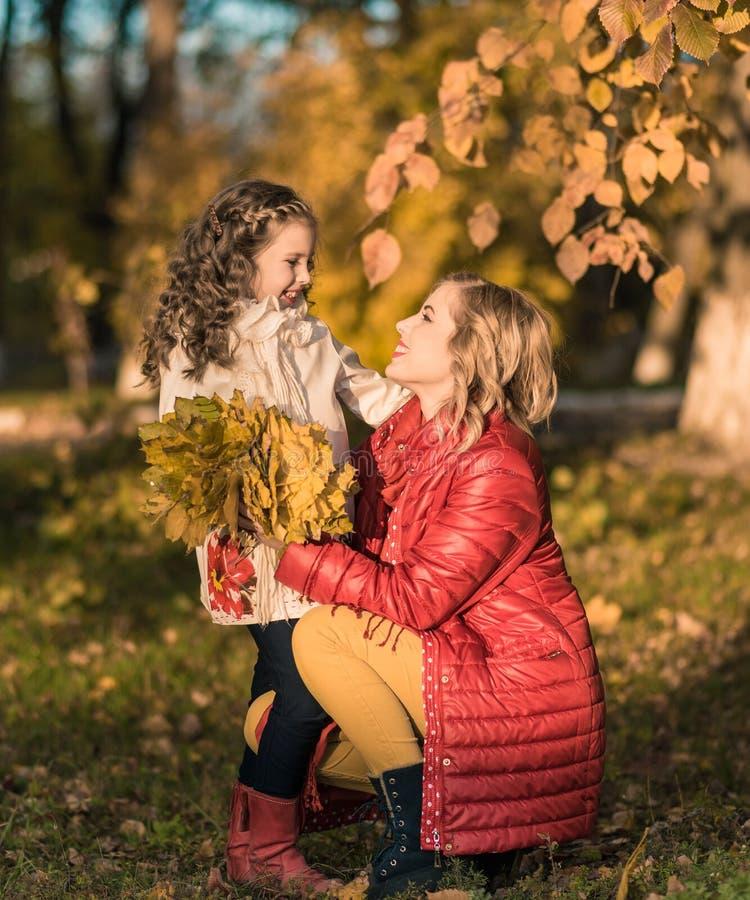 Femme joyeuse heureuse ayant l'amusement avec sa fille dans la couleur d'automne photographie stock libre de droits