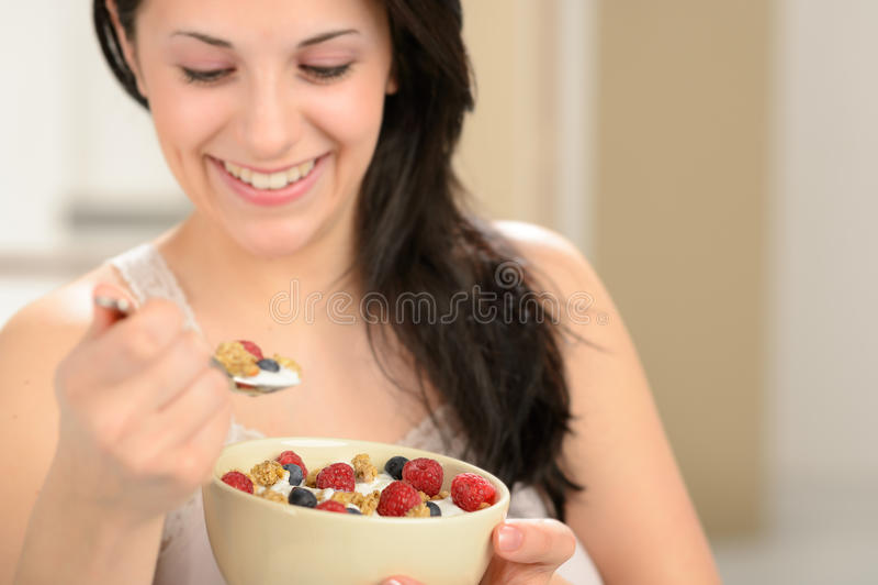 Femme joyeuse mangeant de la céréale saine photographie stock